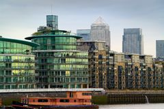 London Offices and apartment blocks. On the river Thames, with Canary Wharf towers in the background, and a barge in the foreground Royalty Free Stock Images