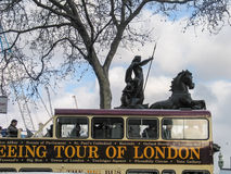 London Open-top Sightseeing Bus Tour moving near Boadicea statue chariot Royalty Free Stock Images