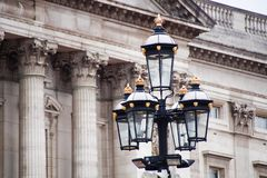 London ornate street light. Ornate lamp post next to old architecture in London England stock images