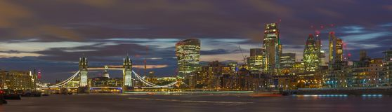 London - The panorama of the Tower bridge, riverside and skyscrapers at dusk with the dramatic clouds Stock Photography