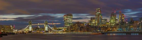 London - panoraman av den tornbron, flodstranden och skyskraporna på skymning med de dramatiska molnen Arkivbild