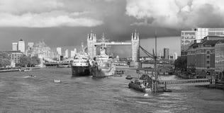 London - panoraman av tornbron, flodstrand i aftonljus med de dramatiska molnen Arkivfoton