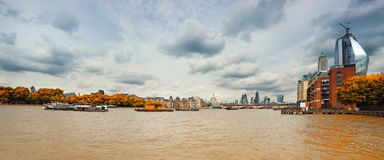 London, panoramic view over Thames on a gloomy day in Fall. London, panoramic view over Thames river from Waterloo bridge on a gloomy overcast day in Fall. This stock images