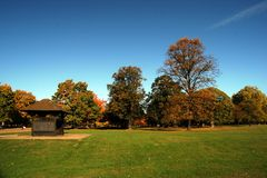London park. Autumn london park with bower, grass, and blue sky royalty free stock photos