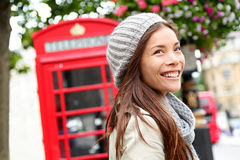 London people - woman by red phone booth. Portrait of beautiful smiling happy young female casual professional business woman walking outside in City of Royalty Free Stock Photography