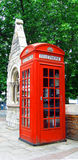 London Phone Booth. Typical British phone booth, seen on a street corner in London outside an old church Stock Photography