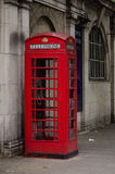 London phone booth. Red telephone booth, on a grey background, just outside the Temple Station in London Stock Images