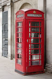 London phone booth. Red telephone booth, on a grey background, just outside the Temple Station in London Stock Photos