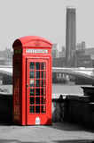 London Phone Box. Red Phone Box, BW London: The phone box in this photo is the original colour, whilst the background has been converted to B&W Royalty Free Stock Image