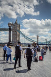 London police on patrol. LONDON, UK - JUNE 11, 2014: Policeman patrol past Tower Bridge on a sunny day Stock Image