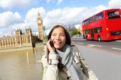 London - professional business woman on smartphone. Smiling happy. Young happy casual woman talking on smart phone walking outdoor in fall or winter on Stock Photo