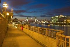 London - promenaden med tornbron och flodstranden på morgonskymning Arkivbild
