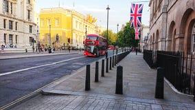 London röda buss- och engelskaflaggor arkivbild