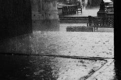London Rain. Greyscale photo of raindrops splashing onto the paving of the London Royal Exchange Royalty Free Stock Image