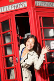 London red phone booth - woman waving happy Royalty Free Stock Photos