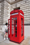 London Red Telephone Box. An unidentified woman enters Red Telephone Box on August 22, 2011 in London, UK. The Red Telephone Box is one of the icons of London Stock Photo