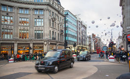 London. Regent street, Oxford circus with lots of pedestrians and cars, taxis on the road. Royalty Free Stock Images