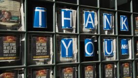A London restaurant displays Thank You NHS posters in the front window. Pan left to right.