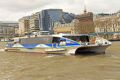 London River Taxi. A river taxi on the famous River Thames that travels through the centre of London, England. The river taxi moves people more swiftly than the stock image