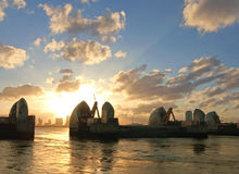 London River Thames barrier. Flood defenses with Canary Wharf skycrapers in the distance Stock Photos
