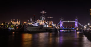 London`s HMS Belfast, Tower Bridge and Tower of London at night Royalty Free Stock Images