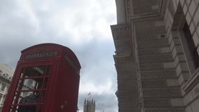 London`s red phone booth. Phone booth- a classic telephone booth ,an old building and a top of Big Ben, London, United Kingdom stock video
