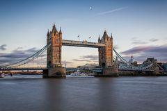 London`s Tower Bridge at sunset with half moon stock images