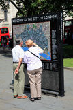 London Sign. London, UK – July 26, 2014 : Elderly couple reading a tourist welcome to London information sign map Stock Photos