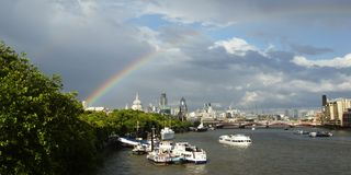 London Skyline. The City of London on a bright sunny day. a passing shower causes a double rainbow to arc over the distant buildings of the city royalty free stock photo