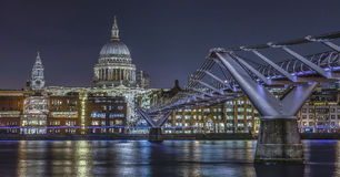 London skyline with Millennium Bridge and St Paul`s Cathedral on. River Thames at night, England Stock Image