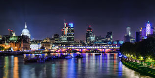 London skyline by night. London skyline at night with lights reflecting from the Thames River stock image