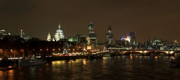 London skyline night scene. Skyline of London viewed illuminated at night over river Thames, London, England stock photo