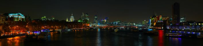 London skyline over the River Thames at night. Panoramic view of London skyline over the River Thames at night Royalty Free Stock Image