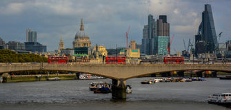 London Skyline with Red Buses. This picture is taken looking across a bridge in London over the Thames River with historic St Pauls cathedral and the new offices Royalty Free Stock Image