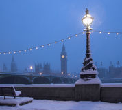 London skyline snow scene. Skyline of London with Big Ben viewed across river Thames at night in winter snow scene, lamp in foreground stock photography