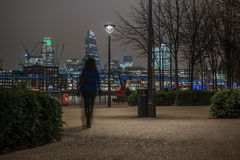 London skyline with an unrecognizable woman walking at night Stock Photo