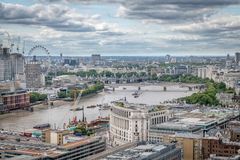 London skyline with a view the Thames looking down river to the Tate modern Parliament and the London eye. On a cloudy day royalty free stock image