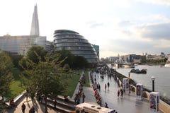 London stadshus, skärvan och flodThemsen med folk som går vid floden Arkivfoton