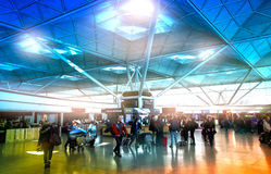 LONDON STANSTED AIRPORT, UK - MARCH 23, 2014: Passengers in the airport departure aria, waiting by the information desk, looking o Royalty Free Stock Photos
