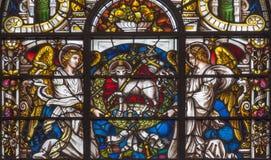 LONDON STORBRITANNIEN - SEPTEMBER 14, 2017: Änglarna och lammet av guden på målat glass i kyrka Royaltyfri Bild