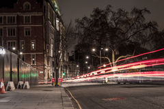 London Street at Night. London street in the middle of the night with light trails from vehicles passing by Royalty Free Stock Photo