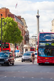 London. The streets of inner London, with Nelsons column in the background. Bikes, busses and taxis all use the busy London roads royalty free stock images