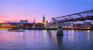 London at sunset, Millennium bridge leading towards illuminated. St. Paul cathedral over Thames river with city bathing in electric light. Panoramic toned image royalty free stock photo