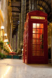 London symbol red phone box in illuminated street. Traditional London symbol red public phone box in illuminated and festively decorated empty trade passage in Royalty Free Stock Images
