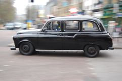 London Taxi. Typical London Taxi racing round the corner ( and almost crashed onto another taxi) near a tube-station Stock Photos