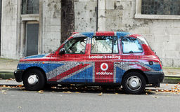 London Taxi. With advertisement of Vodafone a global telecommunications company in London with the design of the British flag Royalty Free Stock Photo