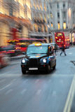 London Taxi. A london taxi with other taxis and a typical London bus in the background.  The image deliberately has lots of zoom blur Royalty Free Stock Photos