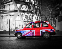 London taxi. Cab at night in the rain with Union Jack flag royalty free stock photography