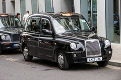 London taxi cab. LONDON - JUL 2, 2015: Row of London Taxis lined up along the sidewalk. The iconic black cabs are a symbol of the city and a major attraction in stock photo