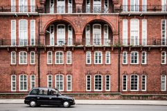 London Taxi in movement and old building Royalty Free Stock Photo